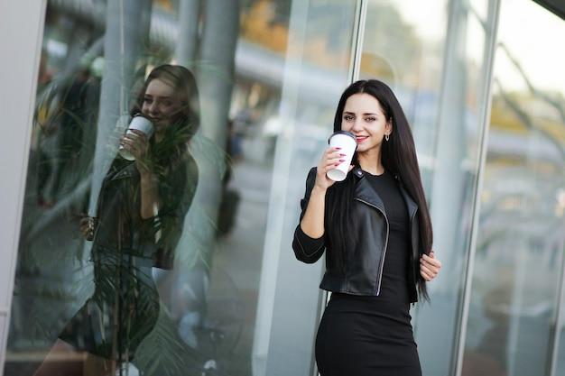 La donna va in viaggio con i bagagli nell'aeroporto internazionale di leopoli e beve il caffè