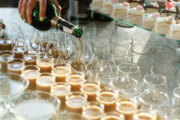 La donna versa il whisky in bicchieri sul tavolo con dolci e alcol
