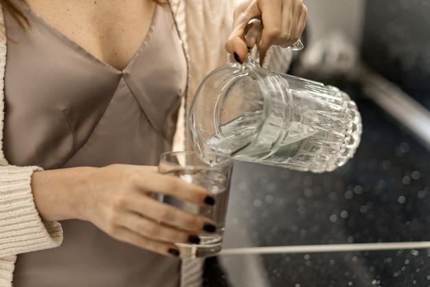 La donna versa l'acqua in un bicchiere da una caraffa di vetro