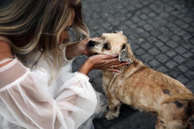 La donna vestita in abito bianco adorabile sta guardando il cane carino