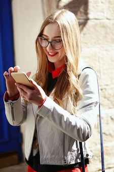 La donna vestita in stile casual controlla il suo telefono in piedi sulla strada