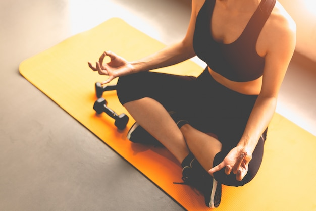 La donna vista dall'alto facendo yoga trigger dito o pagare obedi durante gli allenamenti di fitness