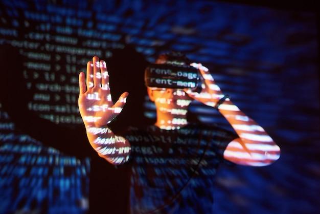 La doppia esposizione di un uomo caucasico e un visore vr per realtà virtuale è presumibilmente un giocatore o un hacker che cracka il codice in una rete o un server sicuro, con linee di codice