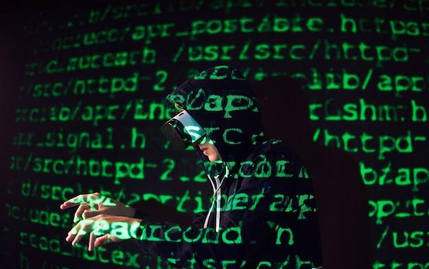 La doppia esposizione di un uomo caucasico e un visore vr per realtà virtuale è presumibilmente un giocatore o un hacker che inserisce il codice in una rete o server sicuro, con righe di codice in verde