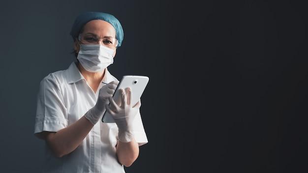 La dottoressa utilizza la tavoletta digitale. la donna in cappotto medico sta su fondo grigio. tecnologia moderna e concetto sanitario. vuoto per banner con emty posto a destra. colpo da vicino. immagine a colori.