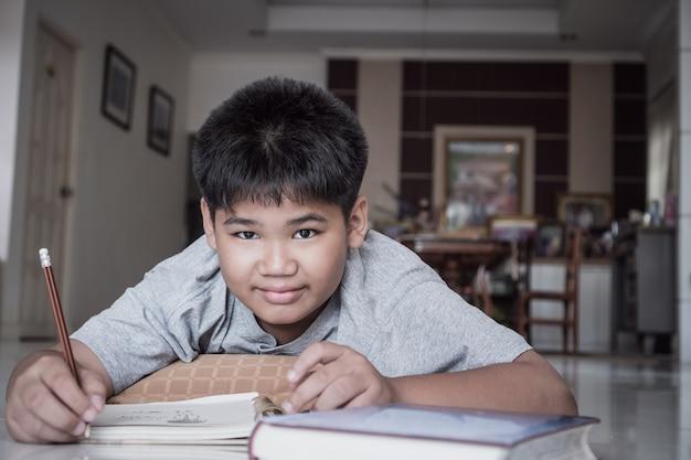 La elementare del ragazzo asiatico dell'allievo del ritratto pone fare i suoi compiti sull'apprendimento del taccuino
