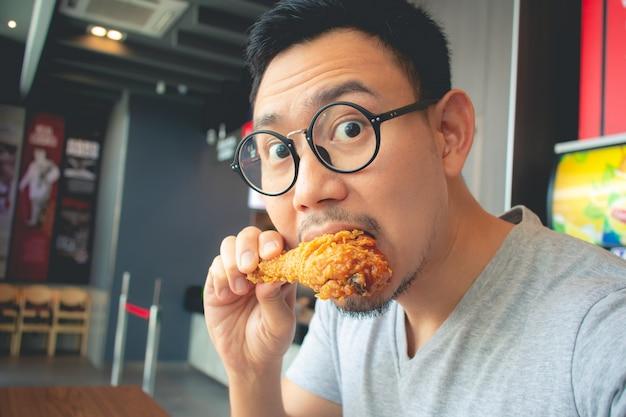 La faccia buffa dell'uomo mangia pollo fritto nel caffè di concessione.