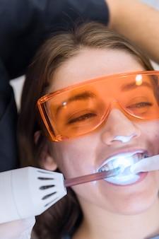 La faccia del paziente femminile che passa con il trattamento sbiancante dei denti del laser