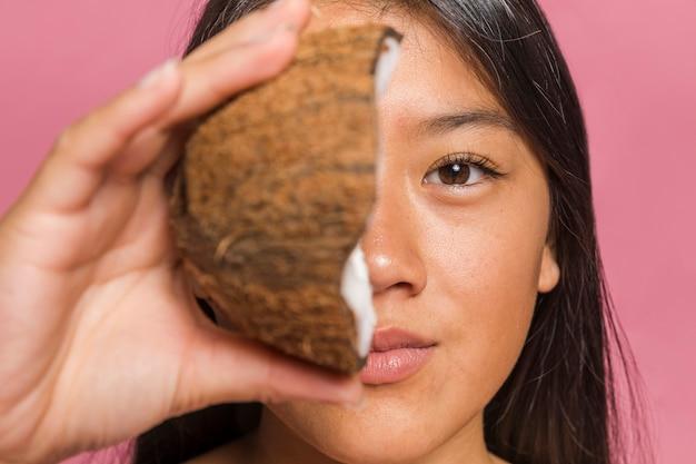 La faccia è coperta da metà della noce di cocco