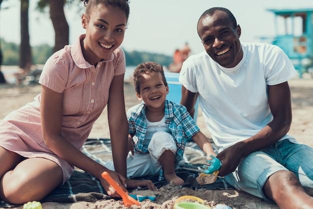 La famiglia afroamericana sta giocando con i giocattoli su sandy shore