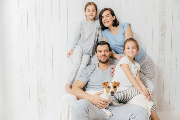La famiglia amichevole posa insieme contro il bianco: due sorelline, padre, madre e il loro animale domestico