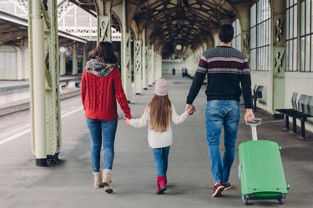 La famiglia amichevole si tiene per mano, porta la valigia, sta per fare un viaggio