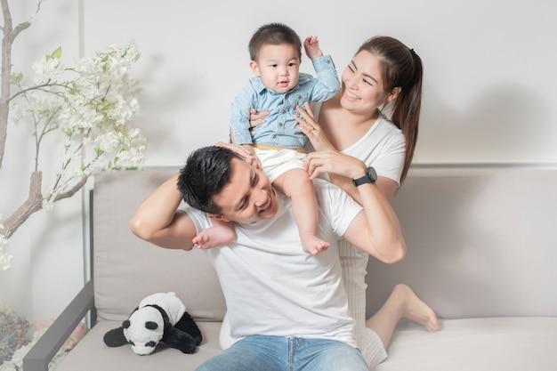 La famiglia asiatica felice si diverte con il figlio a casa