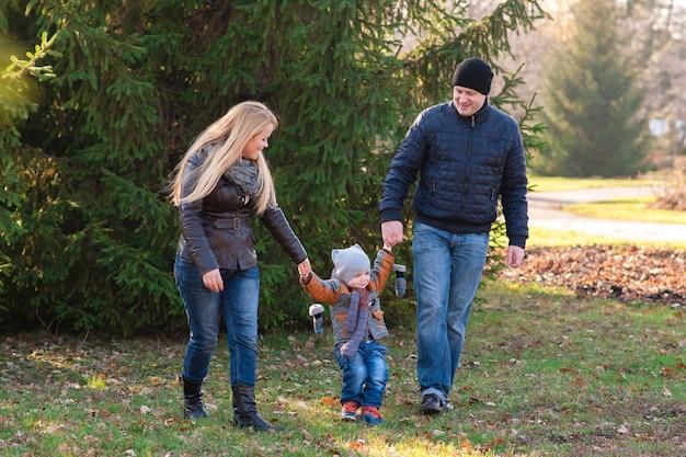 La famiglia cammina nel parco in autunno