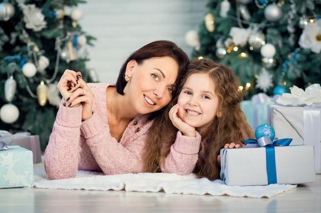 La famiglia celebra il natale. felice madre con figlia. condividere i regali di natale sul piano principale. buon natale e buone feste. tenerezza, cura e comprensione reciproca.