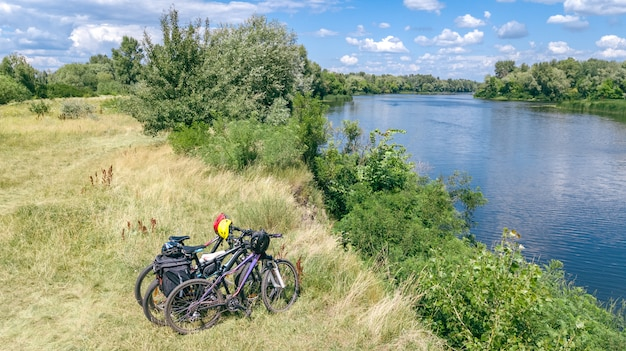 La famiglia che cicla all'aperto, le biciclette si avvicinano al fiume, la vista aerea delle bici e i caschi da sopra, lo sport e il concetto di forma fisica