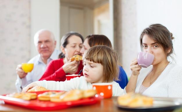 La famiglia comunica intorno alla tabella del tè