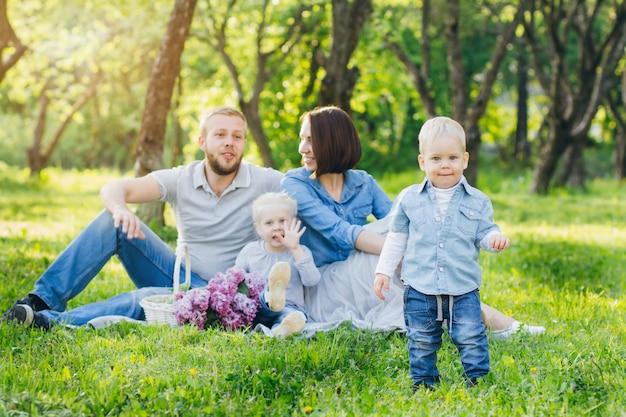 La famiglia con due bambini riposa nel giardino estivo