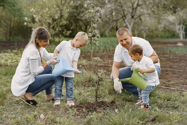 La famiglia con figli piccoli sta piantando un albero in un cortile
