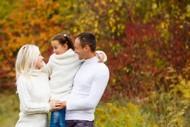 La famiglia con il bambino va nel parco di autunno