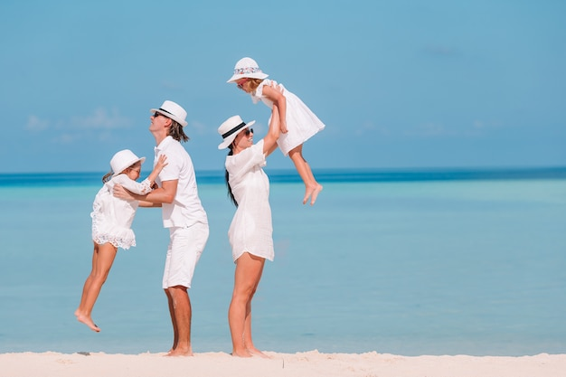 La famiglia di quattro persone in vacanza al mare si diverte