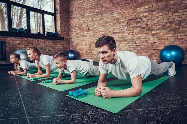 La famiglia di sport fa gli esercizi della plancia in palestra.