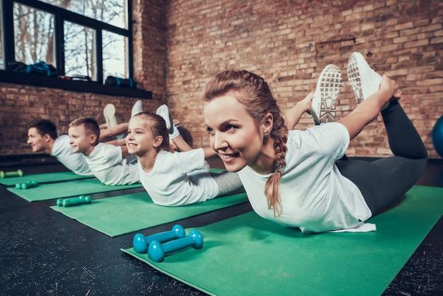 La famiglia di sport fa l'esercizio di canestro nel club di forma fisica.