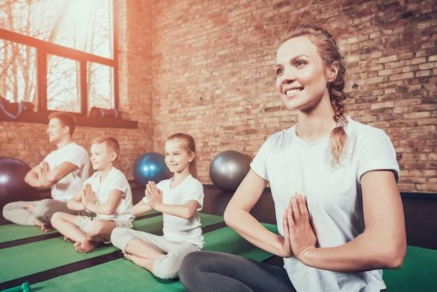 La famiglia di sport ha allenamento di yoga nel fitness club.
