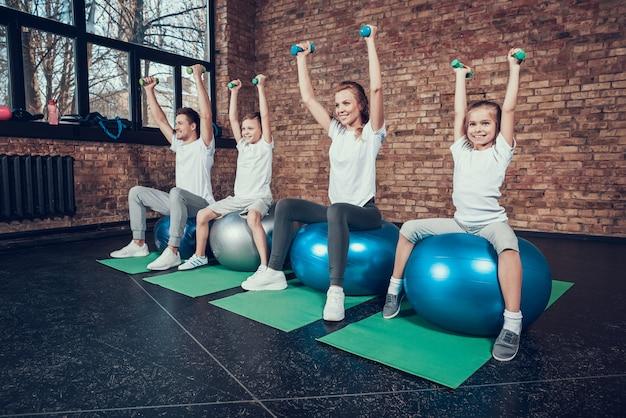 La famiglia di sport lavora con i dumbbells sulle palle di forma fisica.