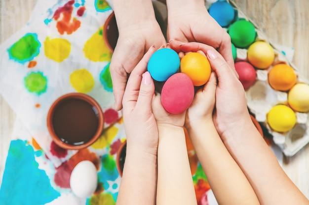 La famiglia dipinge le uova di pasqua. messa a fuoco selettiva celebrazione.