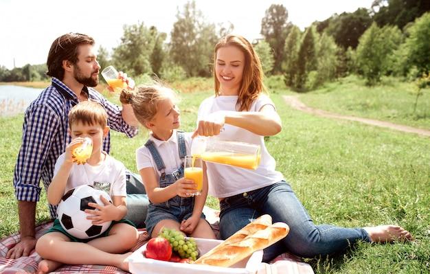 La famiglia è seduta insieme sulla coperta. i ragazzi bevono succo mentre la donna versa del succo nello stomaco della ragazza. entrambe le ragazze stanno sorridendo