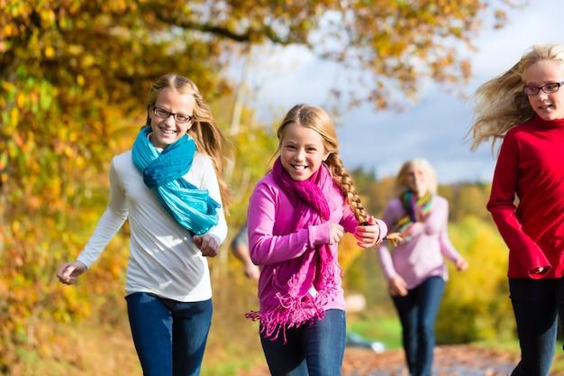La famiglia fa una passeggiata nella foresta di autunno