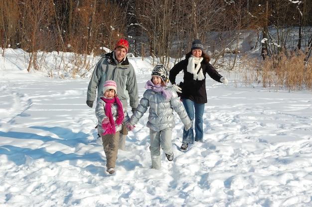 La famiglia felice cammina in inverno, divertendosi e giocando con la neve all'aperto durante il fine settimana di vacanza
