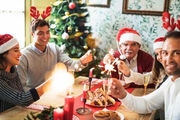 La famiglia felice con gli incendi del bengala burning al tavolo festivo
