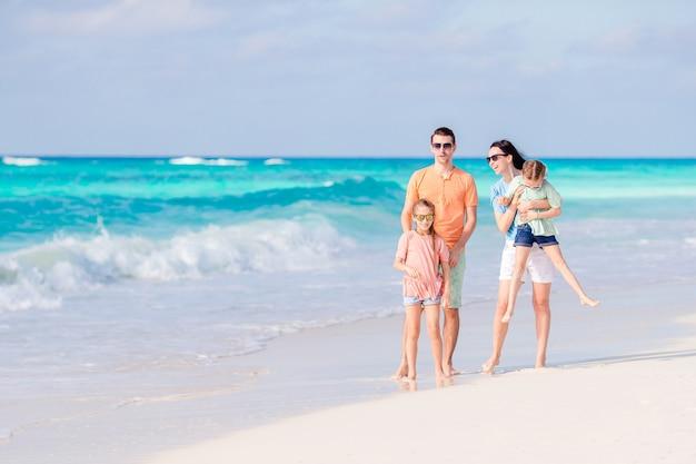 La famiglia felice con i bambini cammina sulla spiaggia al tramonto
