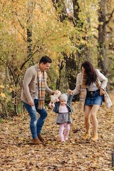 La famiglia felice con il piccolo bambino cammina alla strada del parco con gli alberi gialli all'autunno