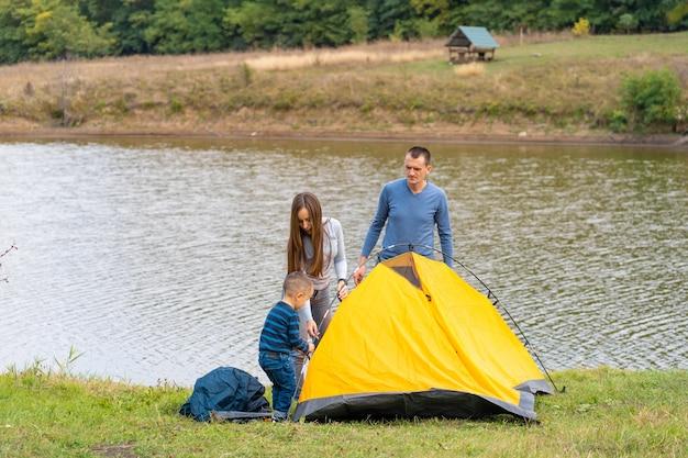 La famiglia felice con il piccolo figlio ha installato la tenda di campeggio. felice infanzia, viaggio in campeggio con i genitori. un bambino aiuta a montare una tenda