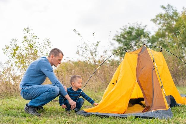 La famiglia felice con il piccolo figlio ha installato la tenda di campeggio
