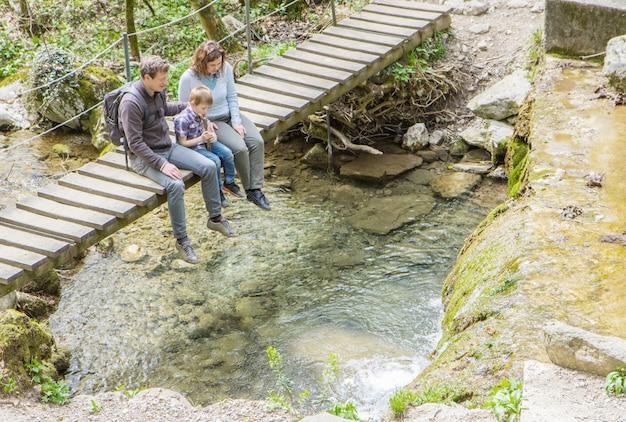 La famiglia felice è seduta su un ponte di legno nel mezzo della foresta