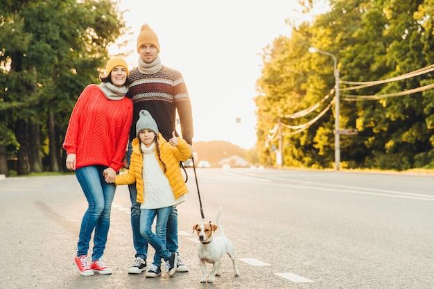 La famiglia felice indossa abiti caldi cammina con il cane sulla strada