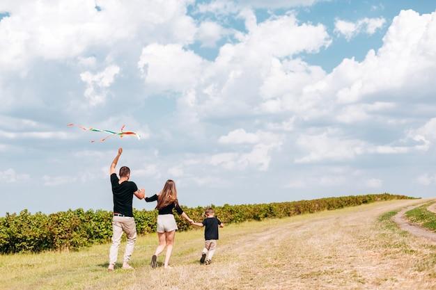 La famiglia felice lancia un aquilone sulla natura.