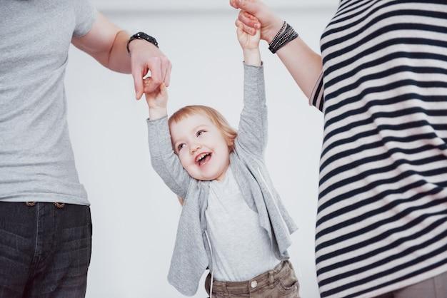 La famiglia felice si diverte a casa. madre, padre e piccolo si tengono per mano