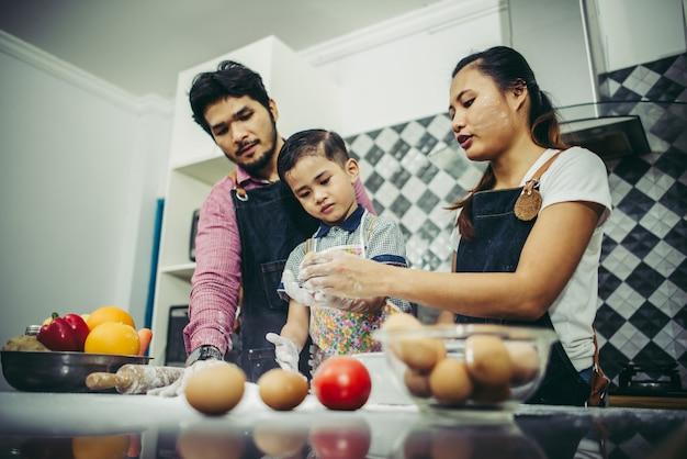 La famiglia felice si diverte a cucinare insieme in cucina a casa. concetto di famiglia