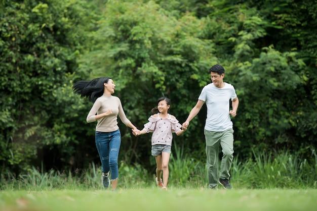 La famiglia felice si diverte madre, padre e figlia stanno correndo nel parco.