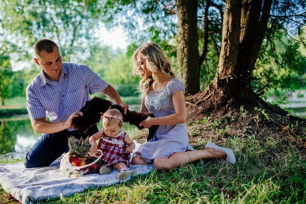 La famiglia felice sta camminando nel parco estivo verde. picnic