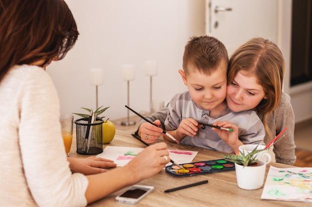 La famiglia felice sta dipingendo su carta