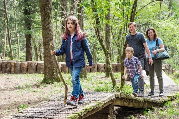 La famiglia felice sta facendo un'escursione nella foresta