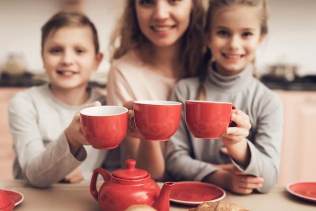 La famiglia felice tiene le tazze rosse ceramiche rustiche.