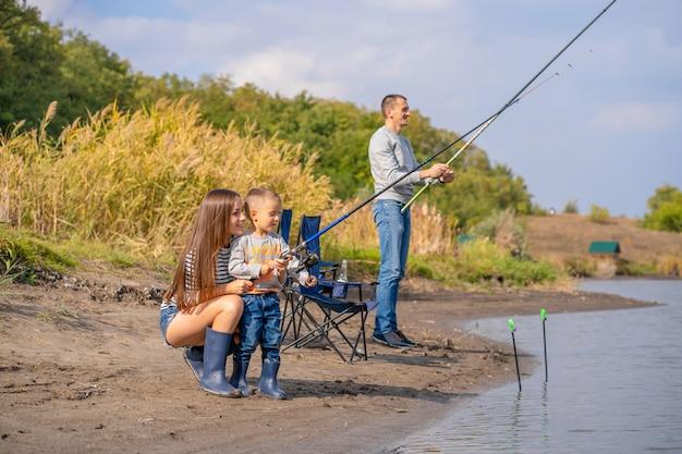 La famiglia felice trascorre del tempo insieme insegnando al figlio a pescare.