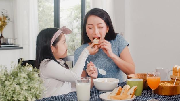 La famiglia giapponese asiatica fa colazione a casa. conversazione felice della figlia e della mamma asiatica insieme mentre mangiando pane, bevendo il succo d'arancia, il cereale dei fiocchi di mais e il latte sulla tavola in cucina moderna nella mattina.